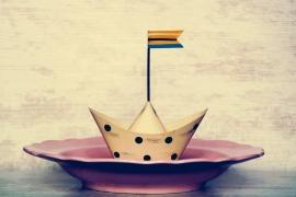 Papierschiff auf einem Teller